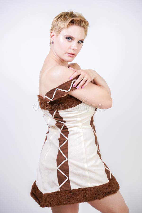 Mulher positiva quente do tamanho no traje do carnaval da pele do homem primitivo no fundo branco no estúdio uma menina selvagem  fotos de stock