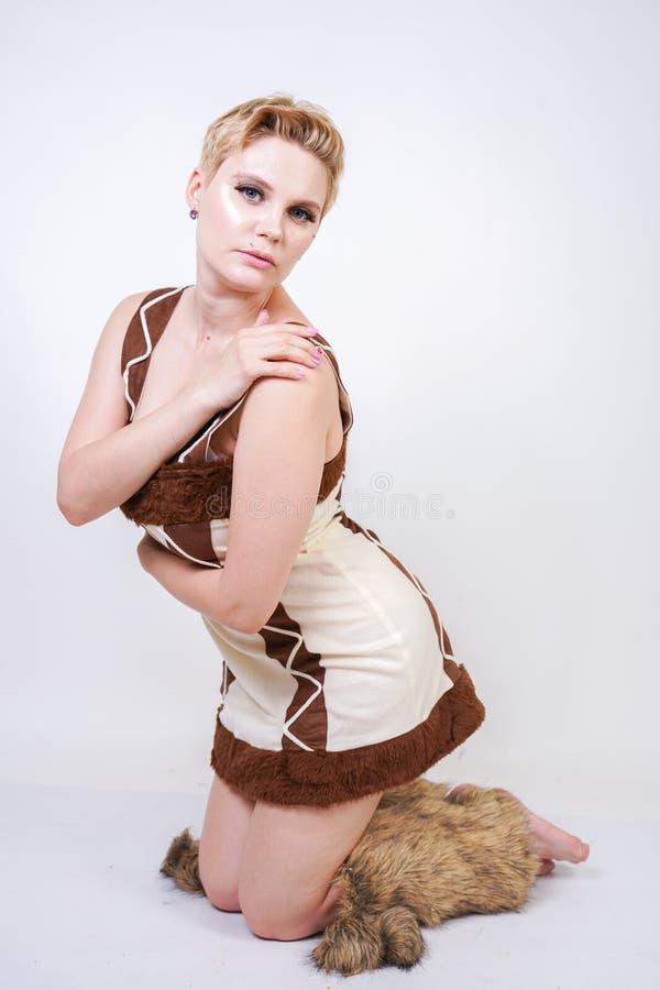 Mulher positiva quente do tamanho no traje do carnaval da pele do homem primitivo no fundo branco no estúdio uma menina selvagem  foto de stock