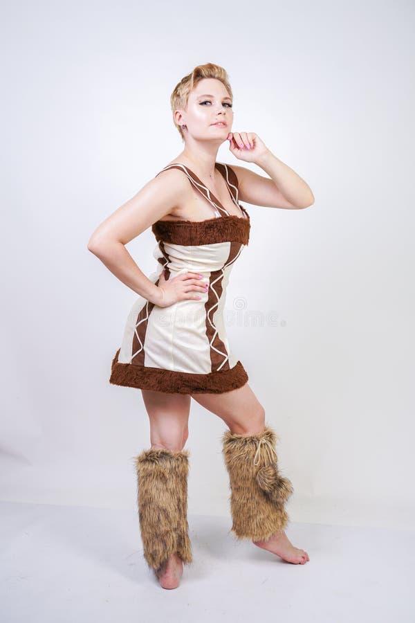 Mulher positiva quente do tamanho no traje do carnaval da pele do homem primitivo no fundo branco no estúdio uma menina selvagem  imagem de stock