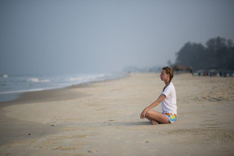 A mulher pratica a ioga imagem de stock
