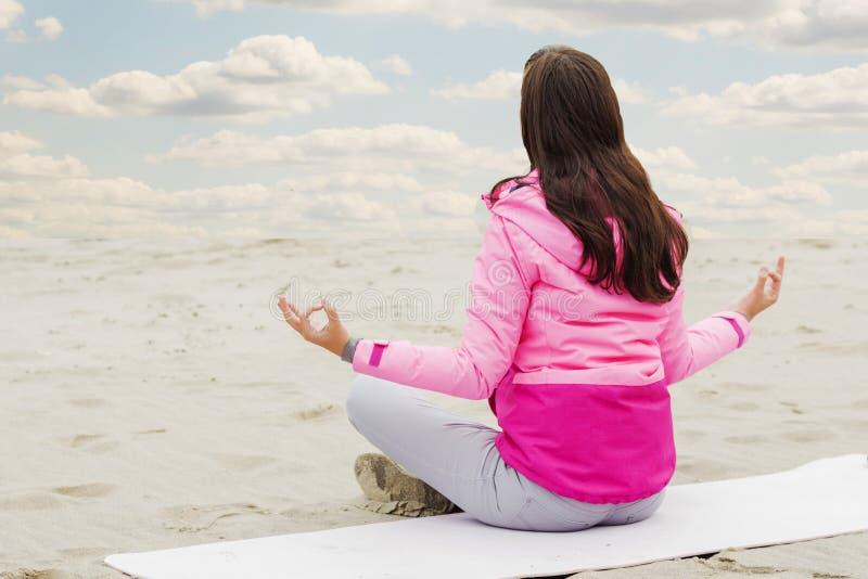 A mulher pratica a ioga e medita na posição dos lótus sobre a praia fotografia de stock