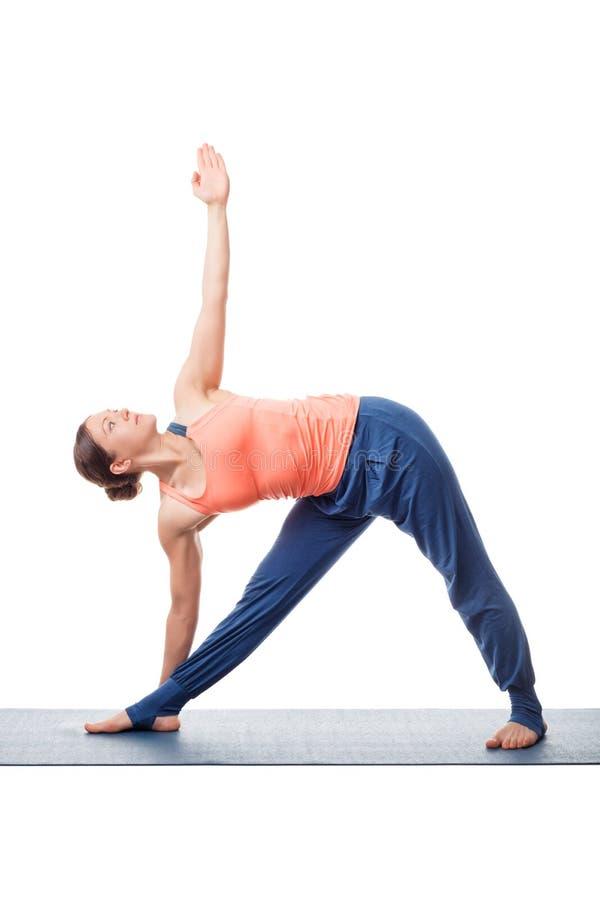 A mulher pratica o trikonasana do utthita do asana da ioga fotografia de stock