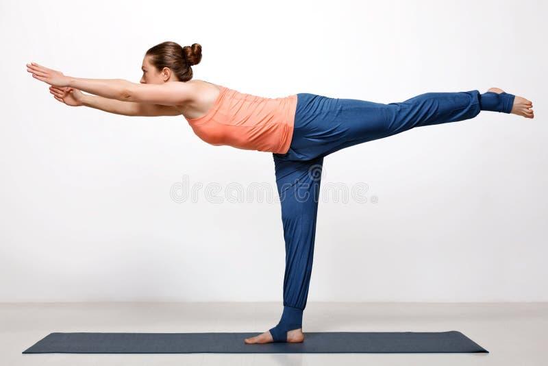 A mulher pratica o utthita Virabhadrasana do asana da ioga foto de stock