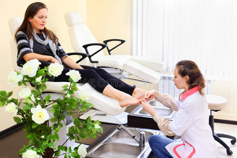 A mulher pratica a quiropodia que toma dos pés fotografia de stock royalty free