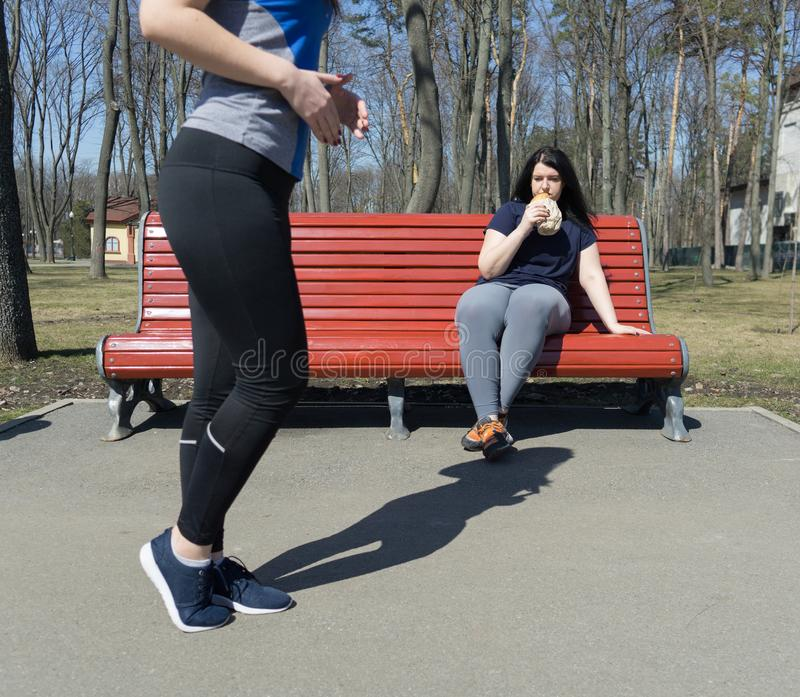 Mulher preguiçosa excesso de peso que come a comida lixo em vez do treinamento Outd fotografia de stock