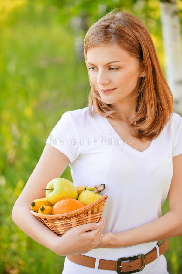 A mulher prende a cesta com fruta foto de stock royalty free