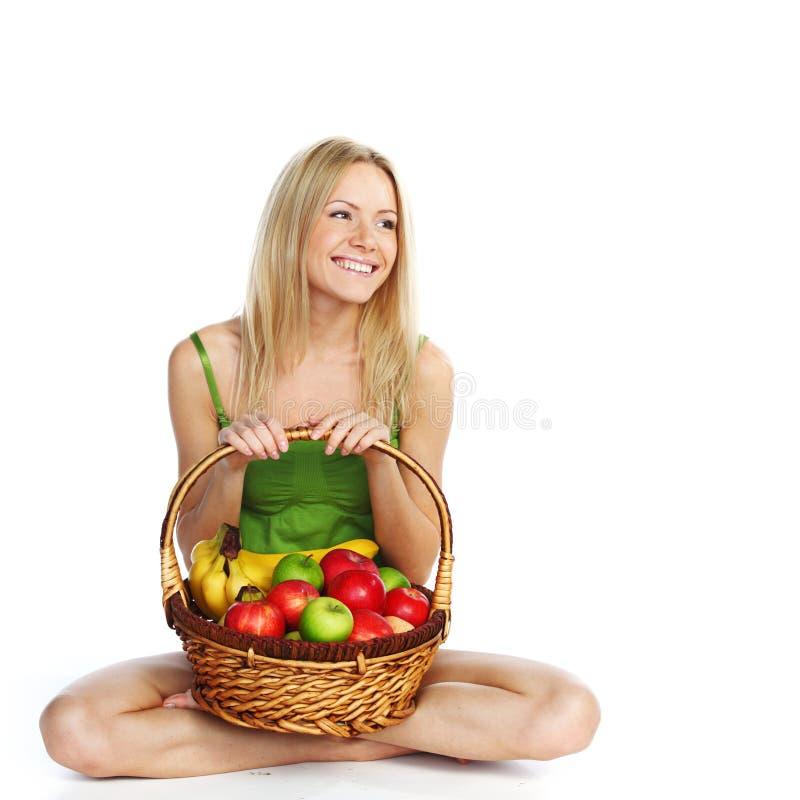 A mulher prende uma cesta da fruta imagem de stock