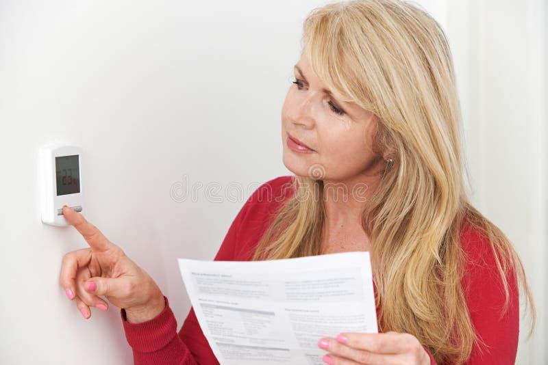 Mulher preocupada com aquecimento de Bill Turning Down Thermostat imagens de stock royalty free