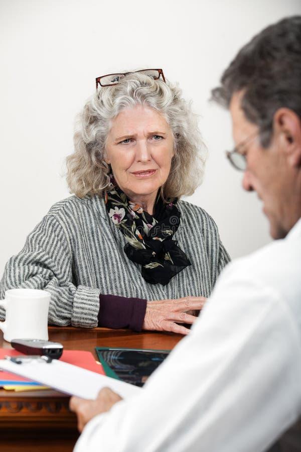 Mulher preocupada que fala com seu doutor fotos de stock