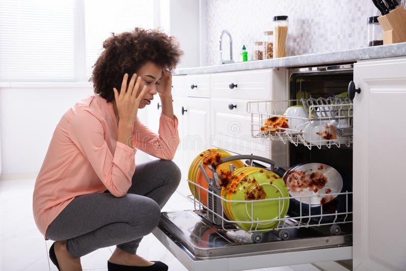 Mulher preocupada que olha as placas sujas na m?quina de lavar lou?a fotografia de stock royalty free