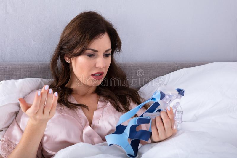 Mulher preocupada que olha a m?scara de CPAP imagem de stock royalty free