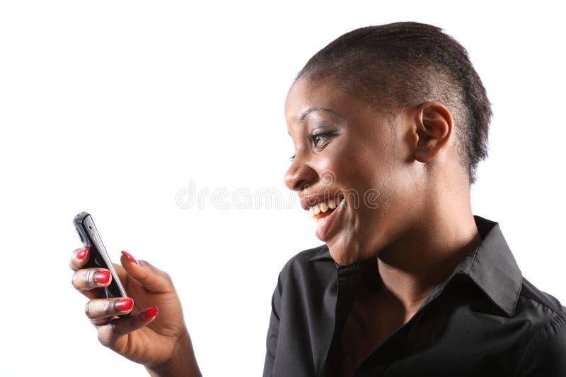 Mulher preta de sorriso bonita que usa o telefone móvel imagens de stock royalty free