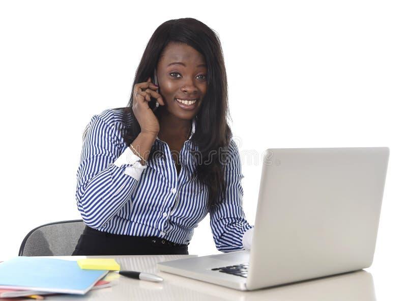 Mulher preta feliz da afiliação étnica que trabalha no portátil e no telefone celular do computador relaxado fotos de stock royalty free