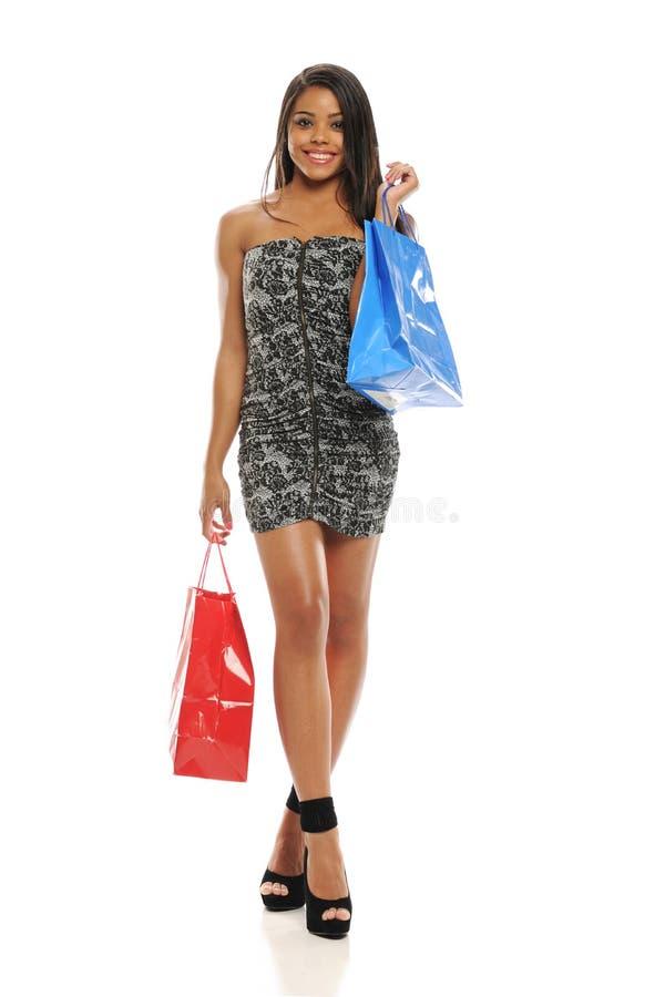 Mulher preta nova com sacos de compra foto de stock