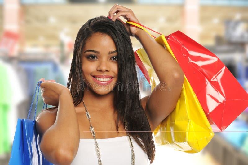 Mulher preta nova com sacos de compra imagem de stock