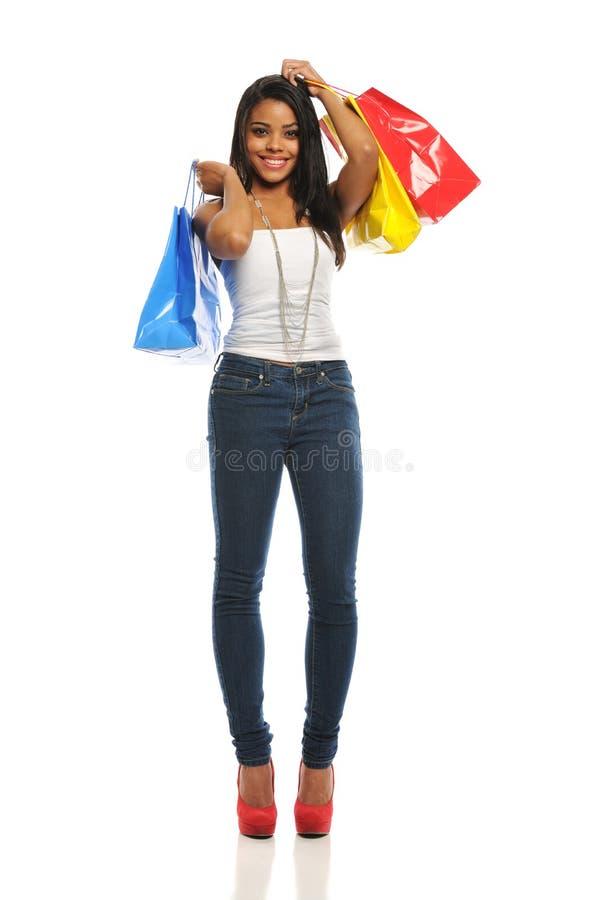 Mulher preta nova com sacos de compra fotografia de stock royalty free