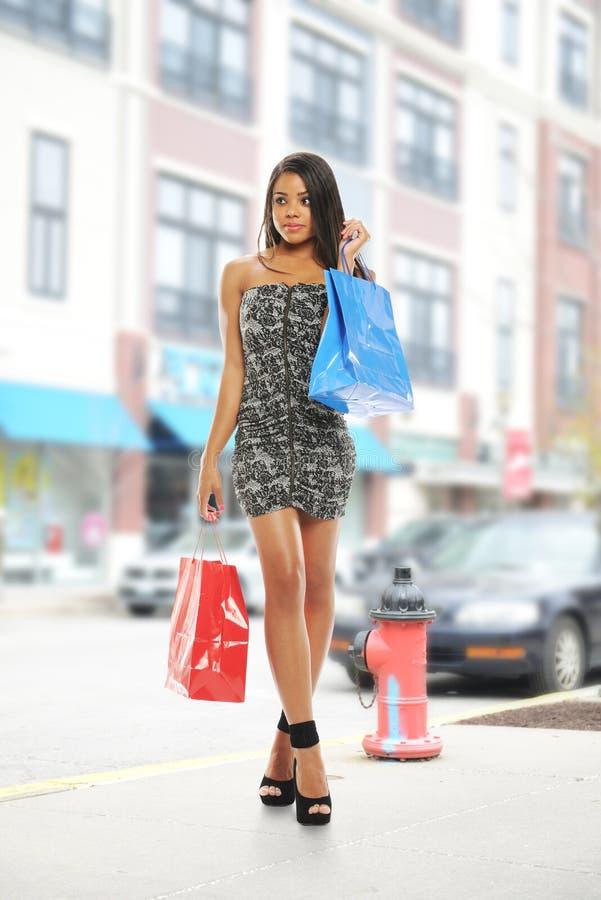Mulher preta nova com sacos de compra fotografia de stock