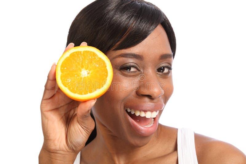Mulher preta nova de sorriso feliz com fruta alaranjada fotos de stock