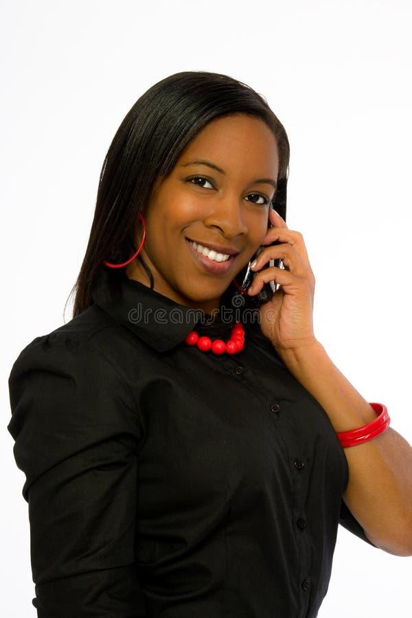 Mulher preta nova de sorriso que fala no telefone móvel. foto de stock