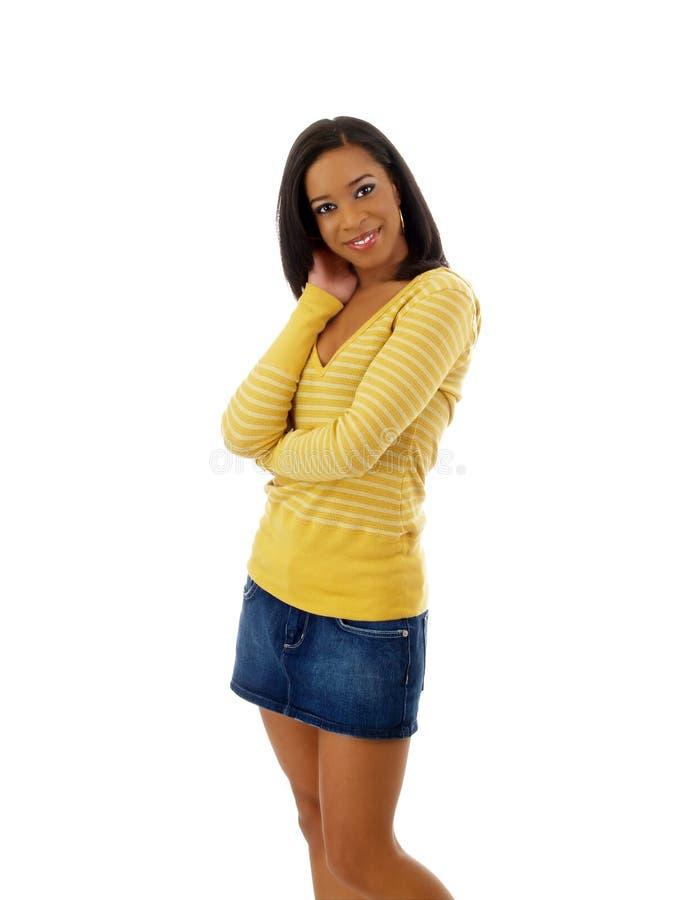 Mulher preta nova na saia amarela da camisola e do brim foto de stock