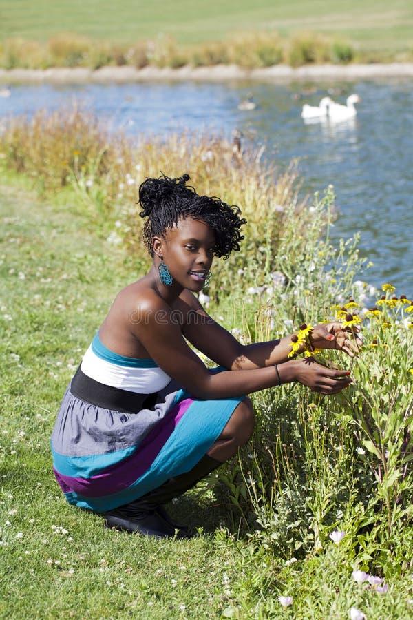 Mulher preta nova que squatting pelo parque das flores imagem de stock royalty free