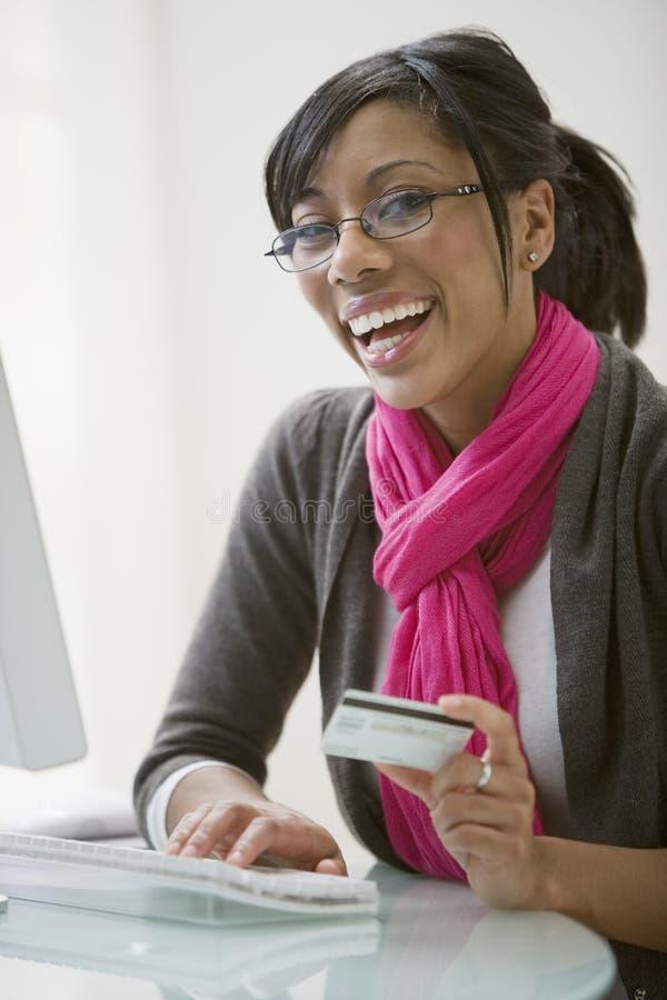 Mulher preta que usa o cartão de crédito para o comércio electrónico foto de stock royalty free