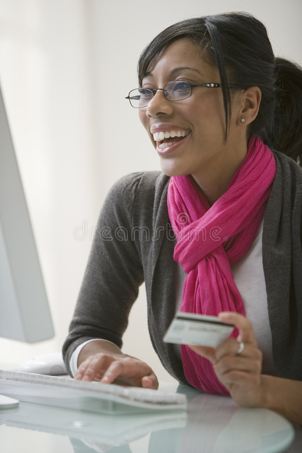 Mulher preta que usa o cartão de crédito para o comércio electrónico fotografia de stock