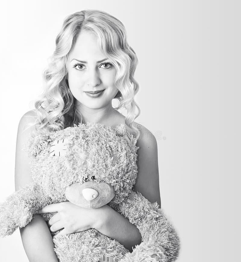 Mulher preto e branco com um urso de peluche imagem de stock