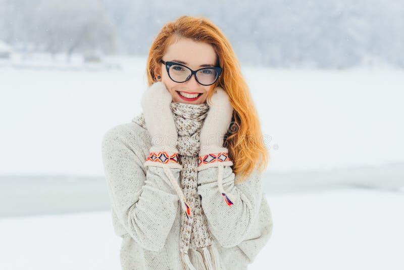 A mulher principal vermelha de sorriso bonita com vidros é envolvida no lenço durante a queda de neve no busto da floresta imagens de stock royalty free