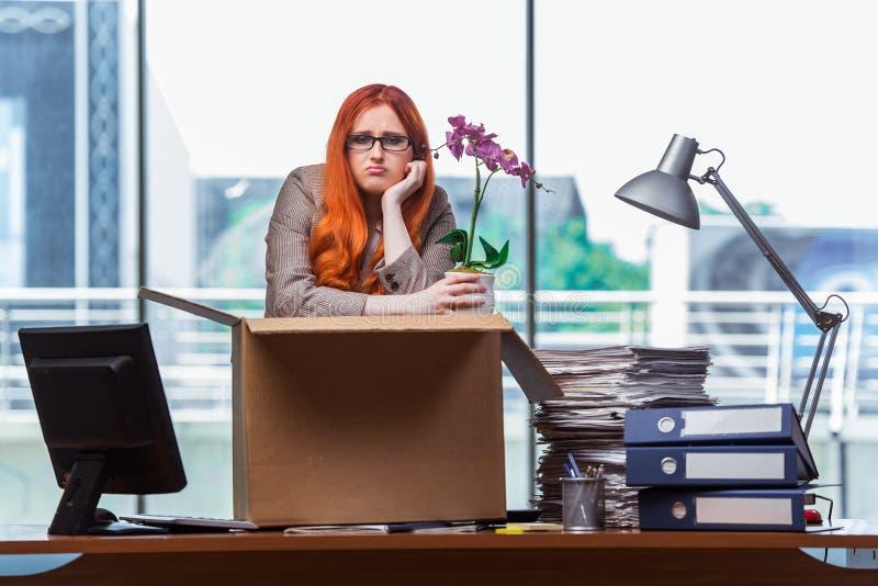 A mulher principal vermelha que move-se para o escritório novo que embala seus pertences imagem de stock