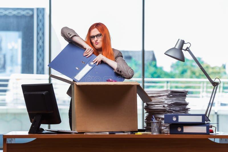A mulher principal vermelha que move-se para o escritório novo que embala seus pertences fotografia de stock