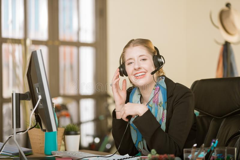 Mulher profissional com cintas em uma chamada dos auriculares foto de stock