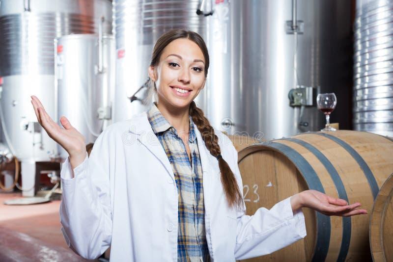 A mulher profissional verifica o vinho na fábrica fotografia de stock