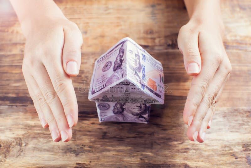 A mulher protege a casa dos dólares Seguro da casa imagens de stock royalty free