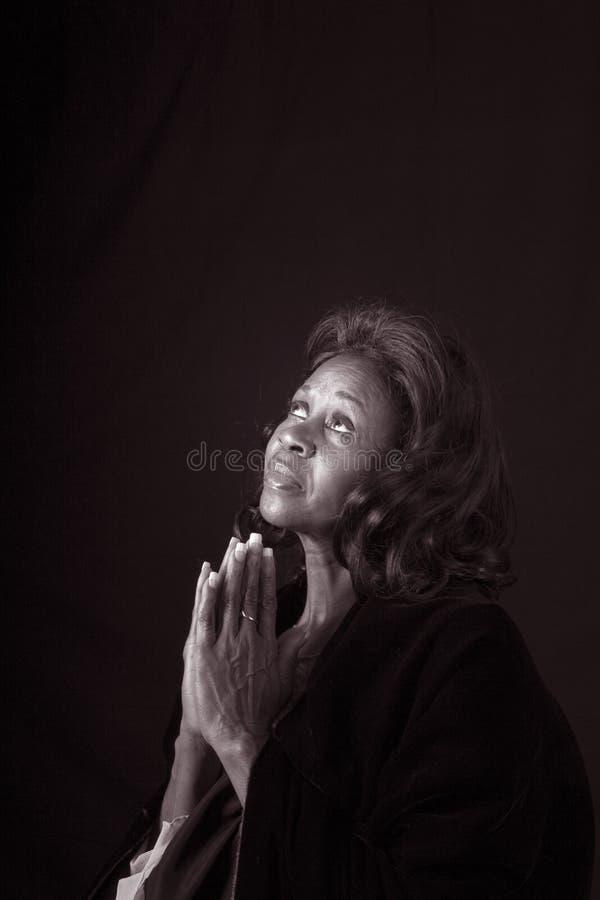 Mulher Pryaing preto e branco fotografia de stock