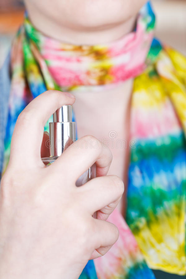 A mulher pulveriza o perfume no lenço de seda do atomizador foto de stock royalty free
