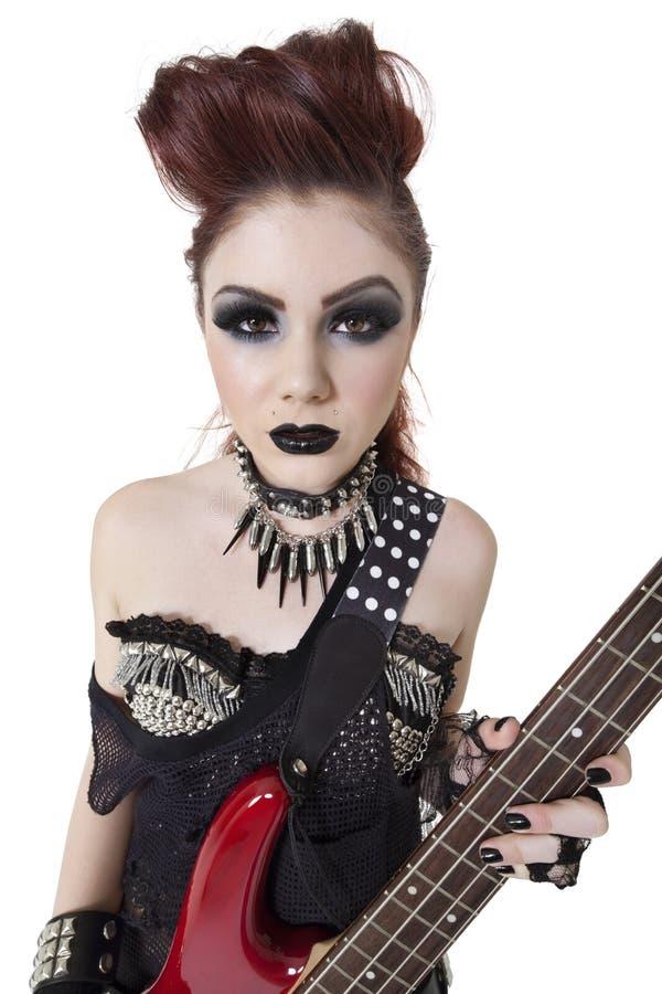 Mulher punk bonita do retrato que olha fixamente ao guardarar a guitarra sobre o fundo branco imagem de stock
