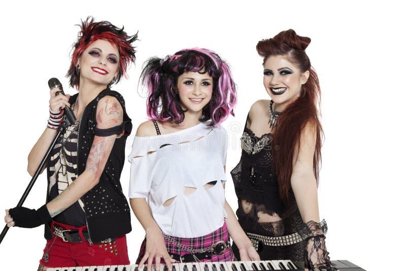 Mulher punk nova bonita com piano e microfone sobre o fundo branco imagem de stock royalty free