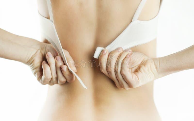 Mulher que abotoa-se desatando um sutiã branco em um fundo branco isolada imagem de stock