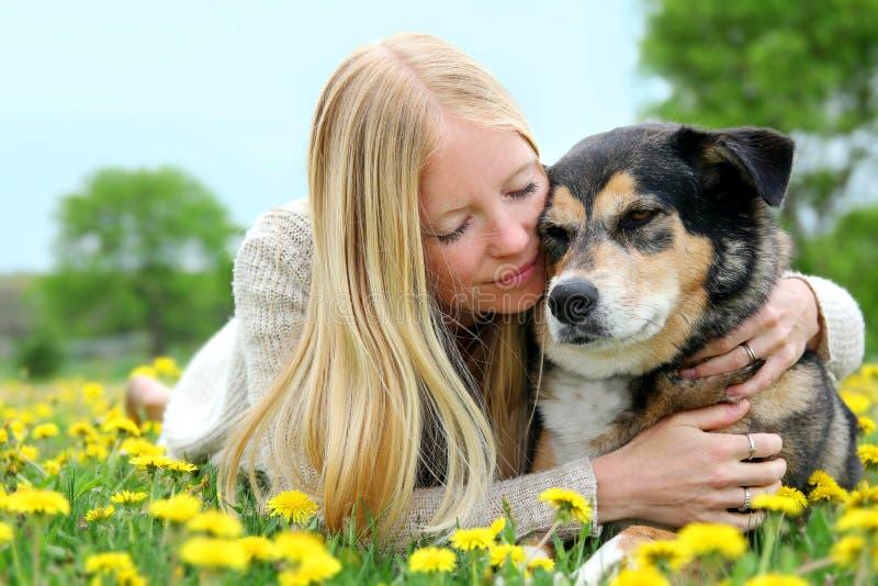 Mulher que abraça maciamente o pastor alemão Dog imagens de stock royalty free