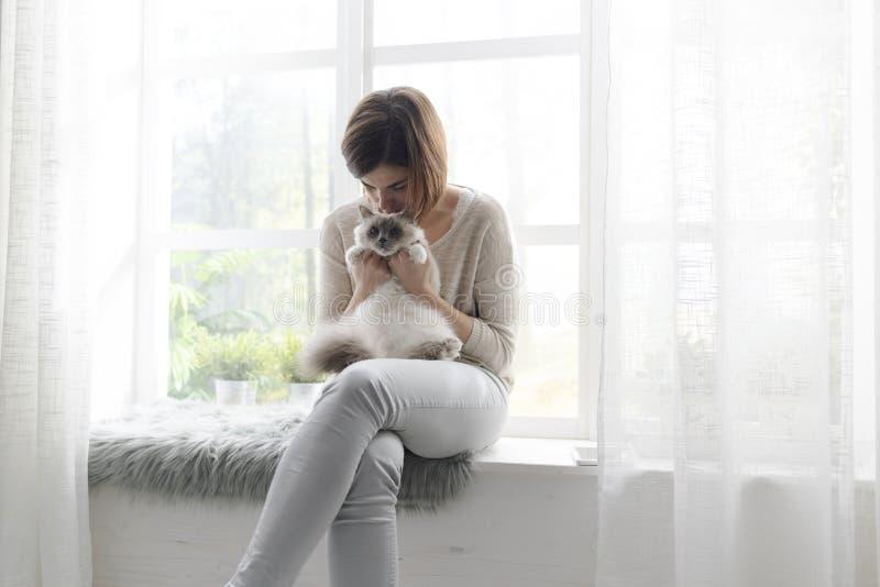Mulher que abraça seu gato bonito em casa fotografia de stock royalty free
