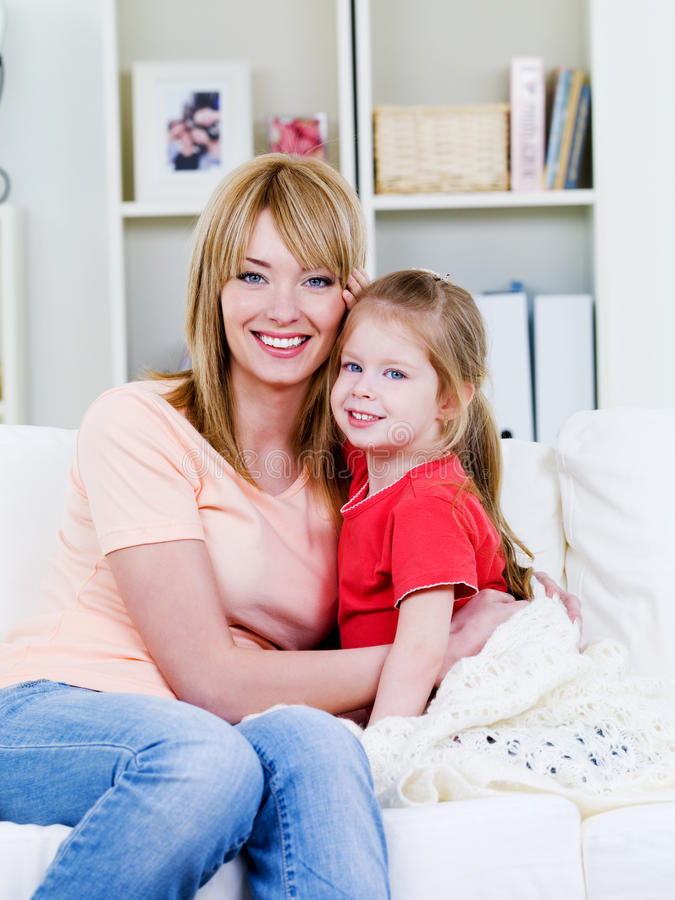 Mulher que abraça sua filha imagem de stock