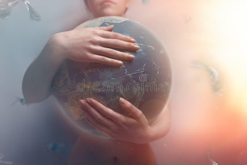 Mulher que abra?a o globo da terra do planeta O conceito de preservar o ambiente e o amor para seu planeta Matiz vermelho e cinze imagens de stock