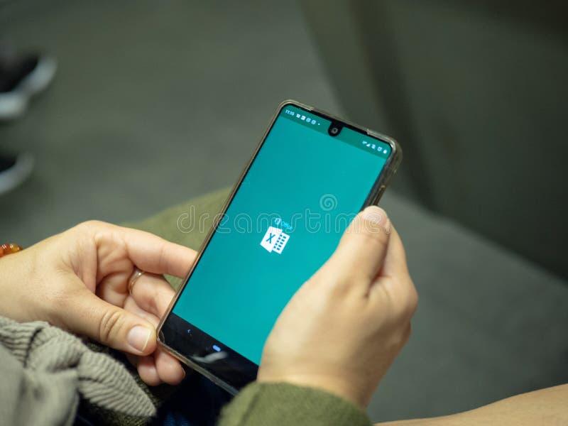 Mulher que abre o app de Microsoft Office 365 Excel com logotipo na tela de Android ao comutar no metro fotografia de stock
