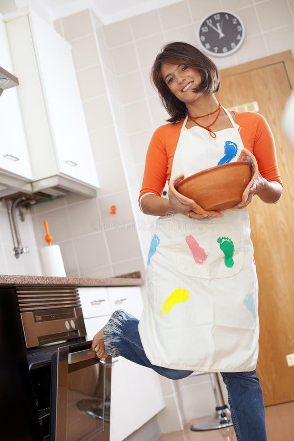 Mulher que abre o forno da cozinha imagem de stock royalty free
