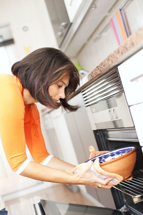 Mulher que abre o forno da cozinha imagens de stock royalty free