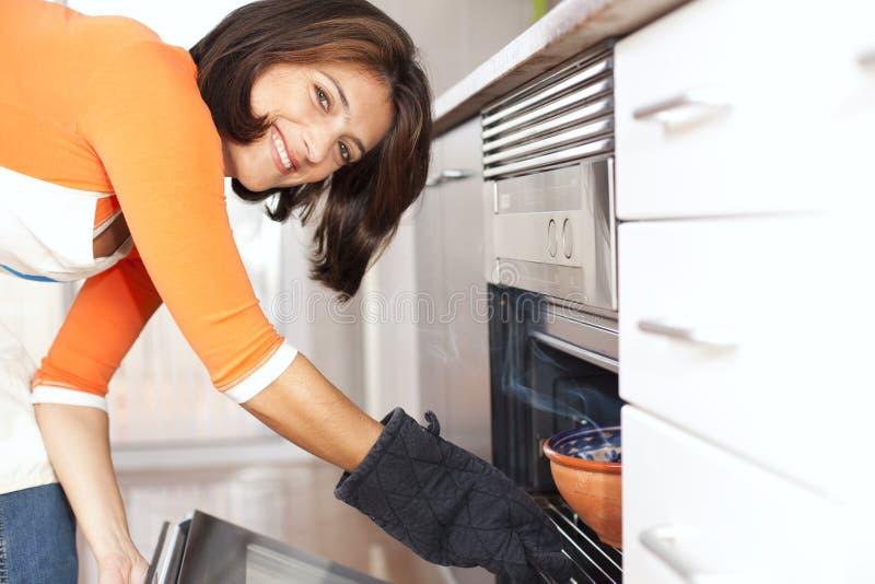 Mulher que abre o forno da cozinha imagem de stock