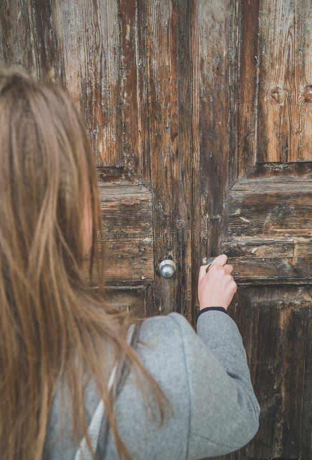 Mulher que abre a porta de madeira muito velha fotos de stock