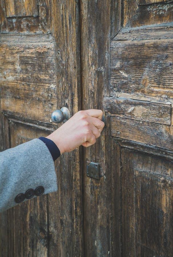 Mulher que abre a porta de madeira muito velha imagens de stock royalty free