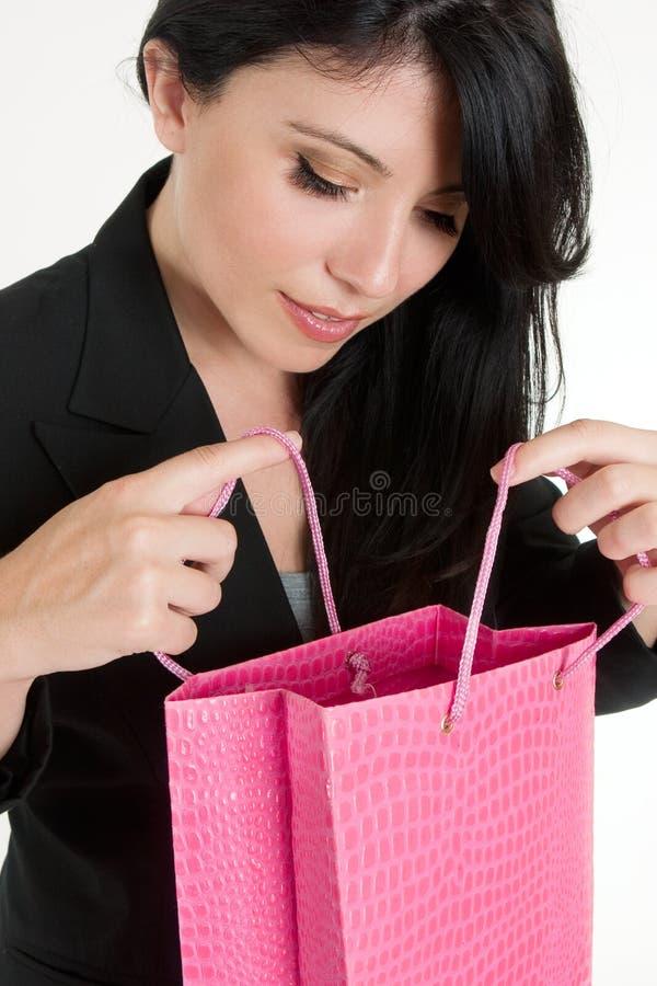 Mulher que abre um saco do presente foto de stock